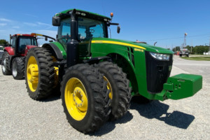 Used tractor John Deere 8360R for sale in equipment lot. Next to other farm machinery for sale